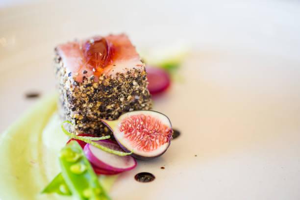 prato de carne de porco gourmet coberto de pimenta esmagada com figos verdes do lado - fine dining - fotografias e filmes do acervo