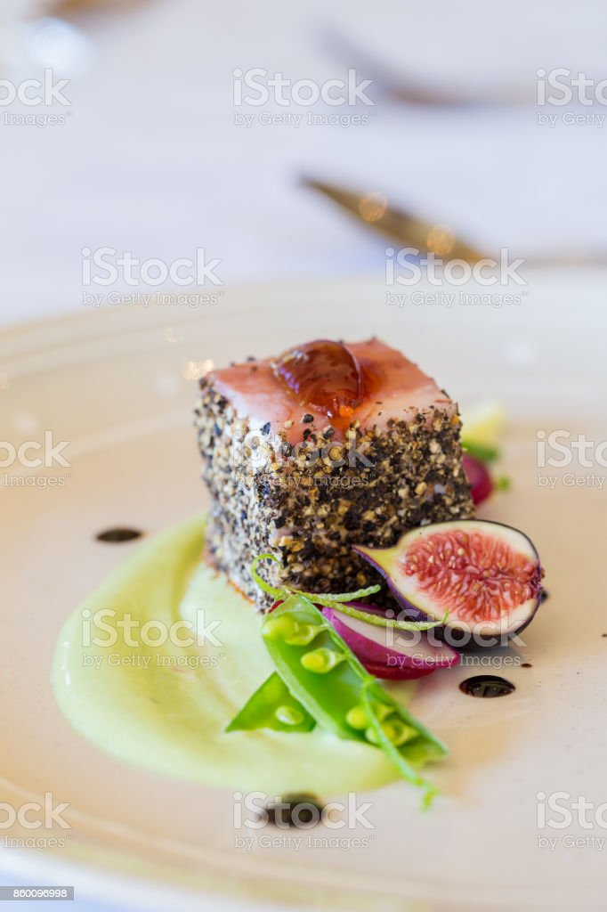 Prato de carne de porco gourmet coberto de pimenta esmagada com figos verdes do lado - foto de acervo