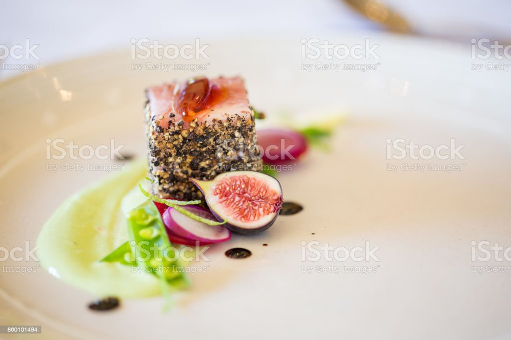 Gourmet pork dish covered in crushed black pepper with green figs on the side stock photo