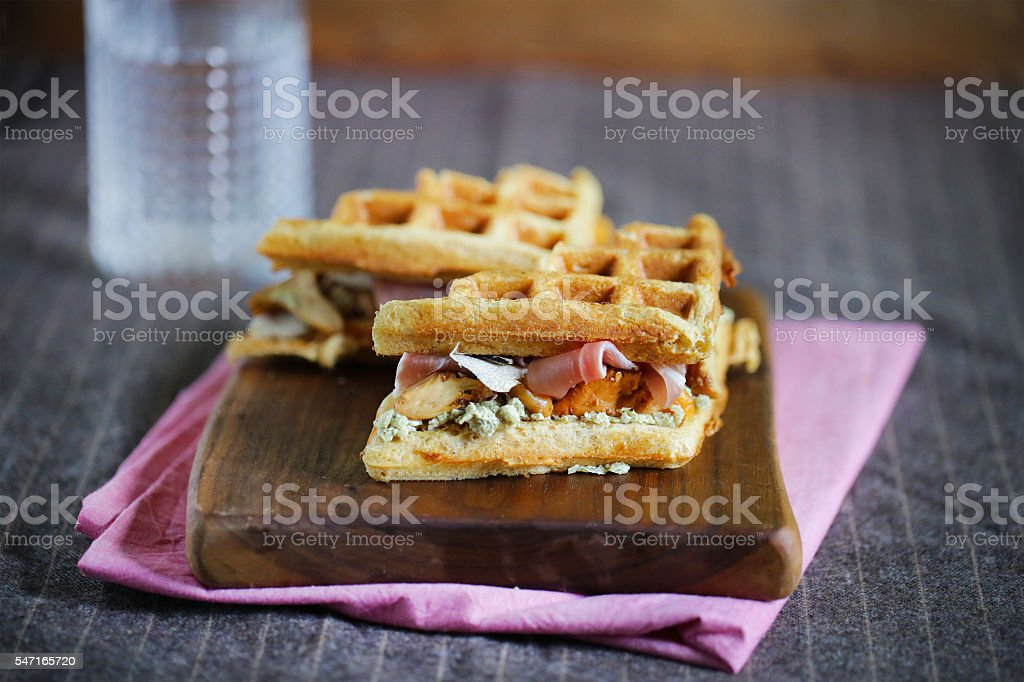 Gourmet sandwich of waffles, prosciutto, cheese and mushrooms stock photo