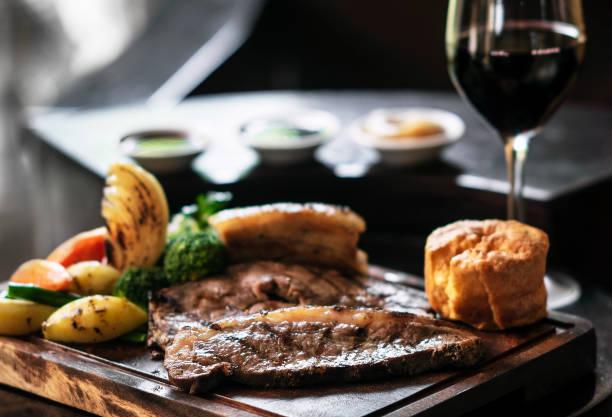 gourmet sunday roast beef traditional british meal set on old wooden pub table - jantar assado imagens e fotografias de stock