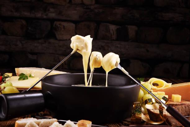 schweizer fondue gourmetdinner an einem winterabend mit sortierten käse - fondue stock-fotos und bilder