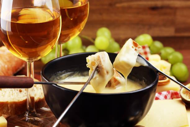 gourmet schweizer fondue abendessen an einem winterabend mit verschiedenen käsesorten auf einem brett neben einem beheizten topf käsefondue mit zwei gabeln tauchen - fondue stock-fotos und bilder