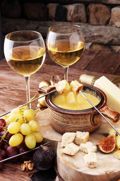schweizer fondue gourmet-dinner an einem winterabend mit verschiedene käsesorten auf einer tafel neben einem beheizten topf mit käse-fondue mit zwei gabeln dippen brot und weißwein hinter in einer taverne oder einem restaurant. - fondue stock-fotos und bilder