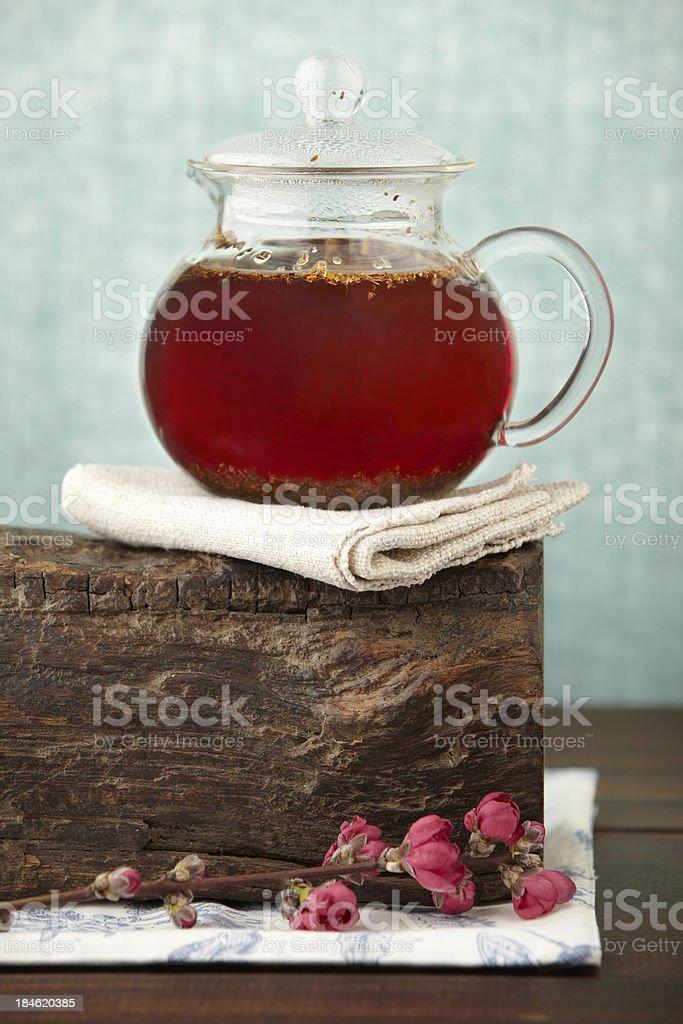 Gourmet tea pot with red herbal rooibos on wood block stock photo
