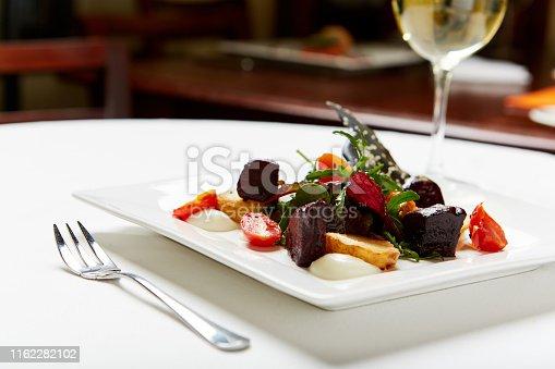Vegan roast beetroot salad in restaurant, served with white wine.