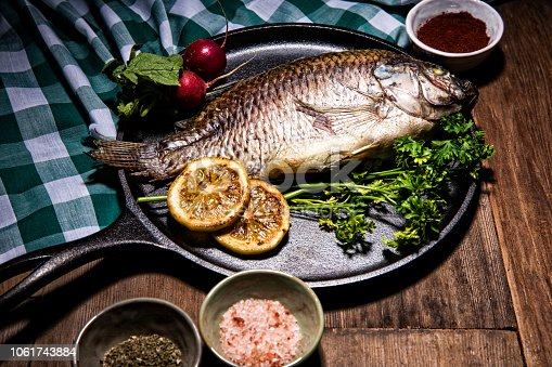 This is a photograph of gourmet Dorado fish on a metal skillet surrounded by colorful spices, lemons, parsley, and radishes in a full frame restaurant table setting. There are no people in the shot. The background is old retro wood with  a green checkered table cloth.