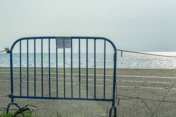 Government forbids walking on the pedestrianized seafront installing railing steal fence with ropes. stock photo