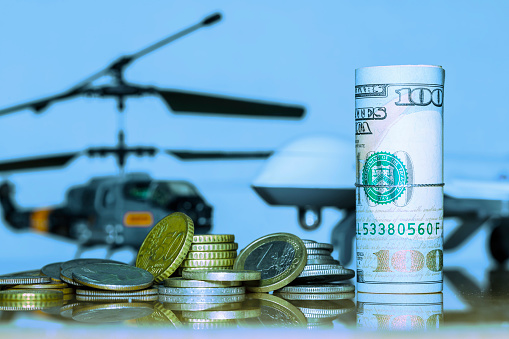istock Government Military Defence Technology Abstract Background, Helicopter And Drone With pile of us dollar and euro coins, Roll of Banknote, Concepts Of Modern Military Operation Cost. 1126180288