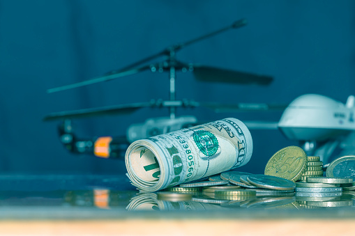 istock Government Military Defence Technology Abstract Background, Helicopter And Drone With pile of us dollar and euro coins, Roll of Banknote, Concepts Of Modern Military Operation Cost. 1126180291