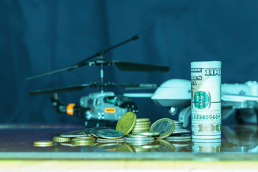 istock Government Military Defence Technology Abstract Background, Helicopter And Drone With pile of us dollar and euro coins, Roll of Banknote, Concepts Of Modern Military Operation Cost. 1126180293