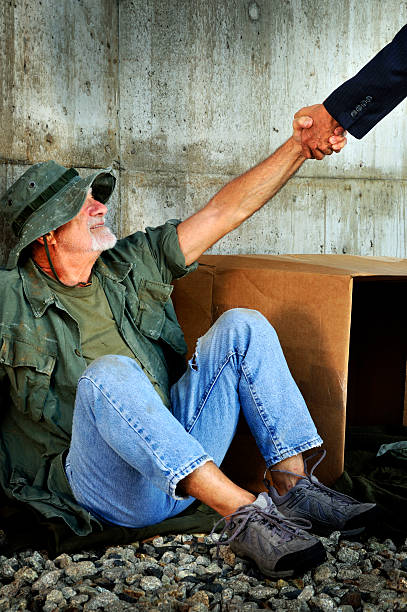 government official giving grateful veteran a hand up - mike cherim stock pictures, royalty-free photos & images