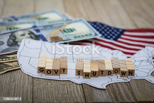 Government Shutdown USA concept with American flag on white background and wooden board.  Concept.  Government.  Funding.