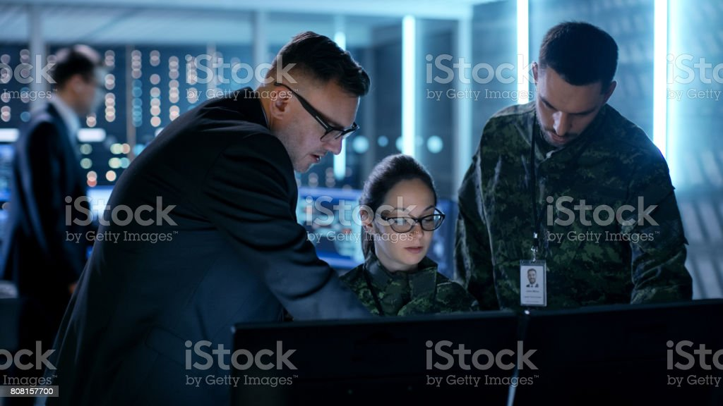 Government Surveillance Agency and Military Joint Operation. Male Agent, Female and Male Military Officers Working at System Control Center. stock photo