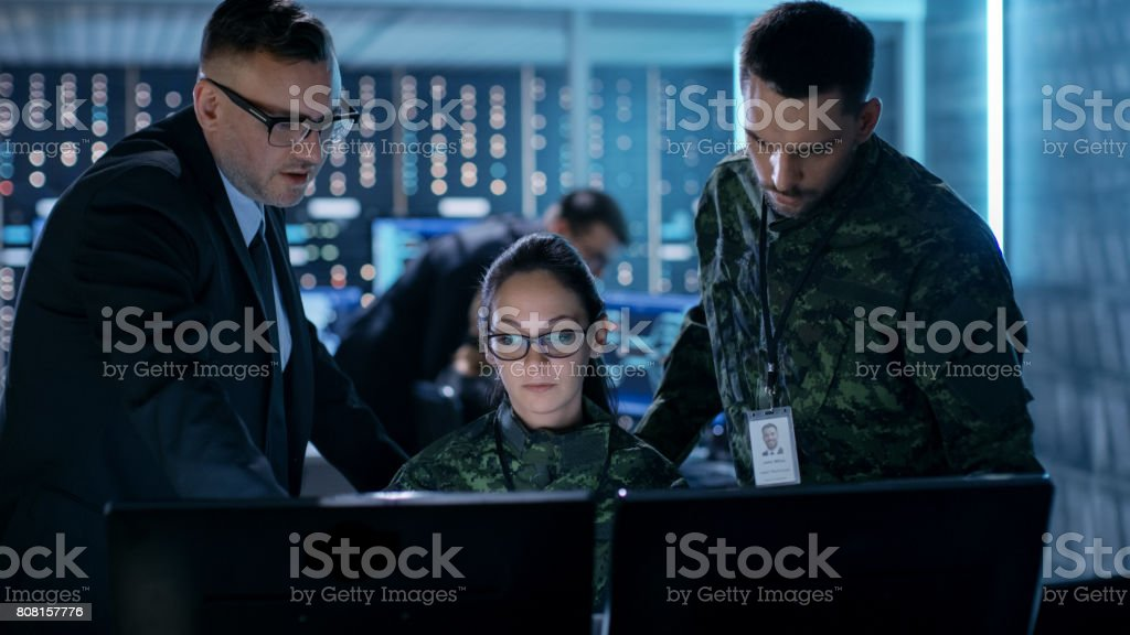 Government Surveillance Agency and Military Joint Operation. Male Agent, Female and Male Military Officers Working at System Control Center. Government Surveillance Agency and Military Joint Operation. Male Agent, Female and Male Military Officers Working at System Control Center. Adult Stock Photo