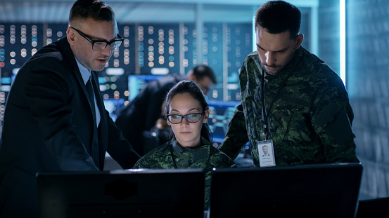 Government Surveillance Agency And Military Joint Operation Male Agent Female And Male Military Officers Working At System Control Center Stock Photo - Download Image Now