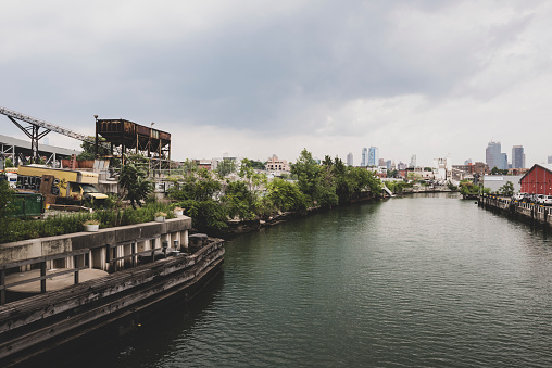 New York City, USA - July 7, 2016: View of the Gowanus Canal from the 9th Street bridge in Brooklyn. One of the most polluted waterways in the United States, it was designated a Superfund site in 2009.