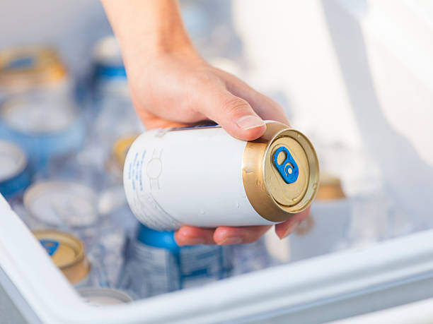 Grab a Cold Beer from the Cooler Grabbing a nice cold beer out of a cooler on a warm Summer afternoon. The label has been partially removed due to copyright content. cooler container stock pictures, royalty-free photos & images
