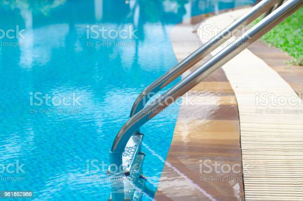 Photo of Grab bars ladder in the blue swimming pool