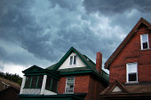"""""""Thick fluffy clouds float over older-style houses.  2 minutes after this photo was taken, there was a very big storm."""""""