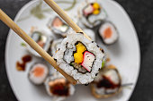 Grabbing a california roll japanese food with chopstick - top view