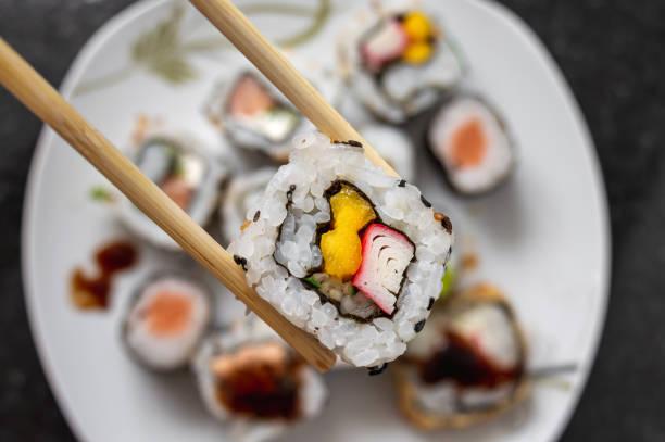 カリフォルニア ロールの日本食を箸でつかんでください。 - 日本食 ストックフォトと画像
