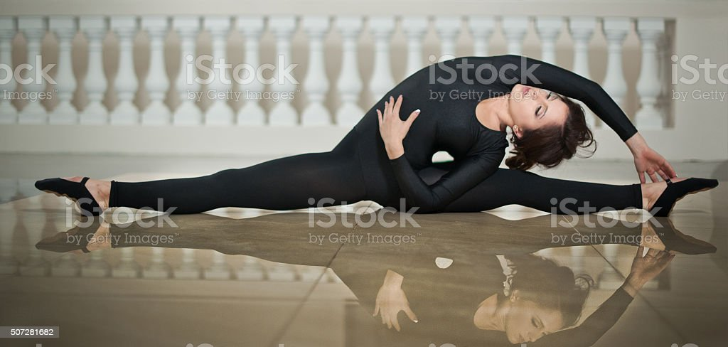 Graceful ballerina doing the splits on the marble floor stock photo