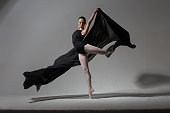 Graceful ballerina posing with a black cloth. Studio photography. The concept of beauty and grace.