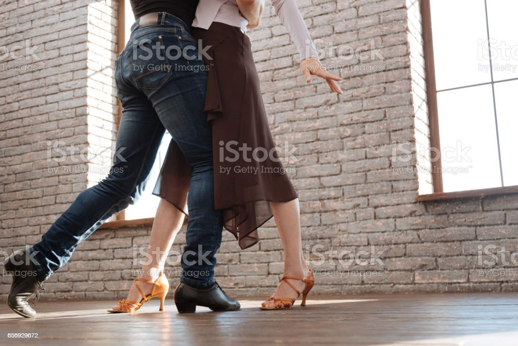 Graceful dance couple tangoing at the ballroom stock photo