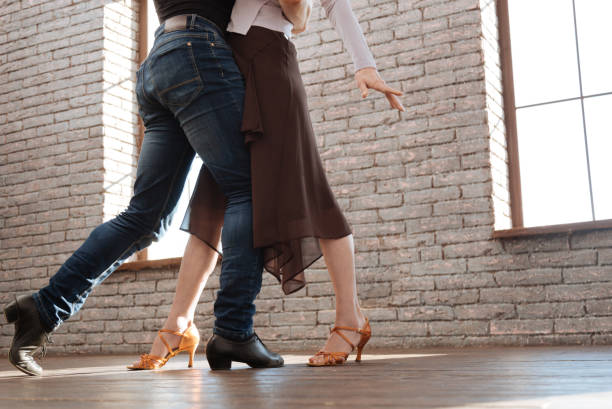 graceful dance couple tangoing at the ballroom - dance class stock photos and pictures