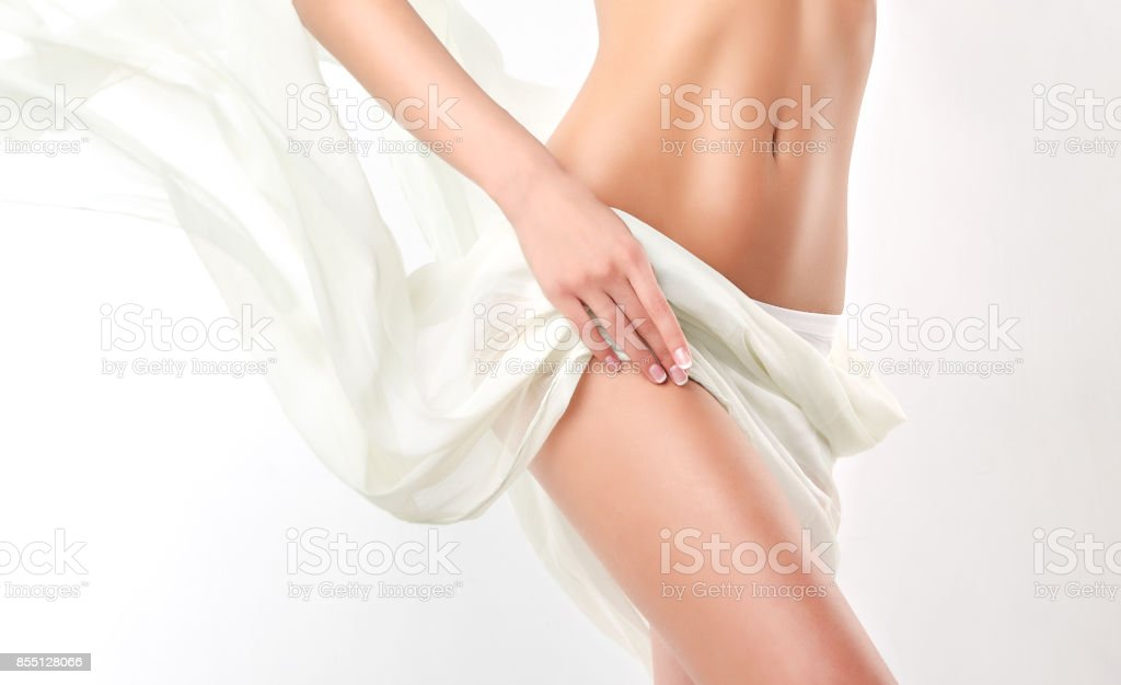 Graceful female body covered by tender, silk textile.  Alluring and healthy woman belly and hips.. stock photo
