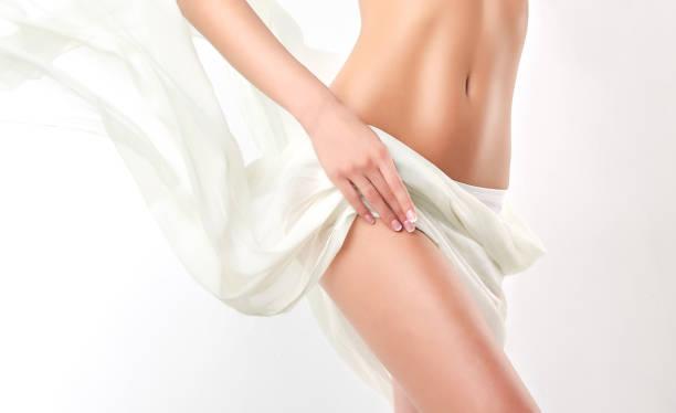 優美な女性の身体は柔らかく、絹の織物で覆われて。 魅惑的で健康的な女性の腹と腰. ストックフォト