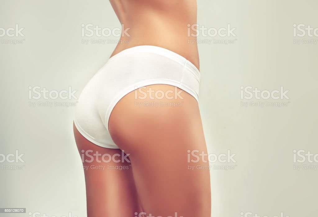 Graceful female body dressed in a white underwear pants. Attractive, well shaped woman buttocks. stock photo