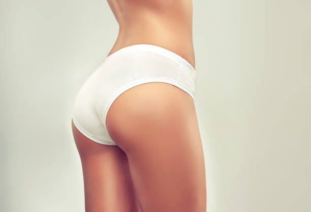 graceful female body dressed in a white underwear pants. attractive, well shaped woman buttocks. - buttock stock photos and pictures