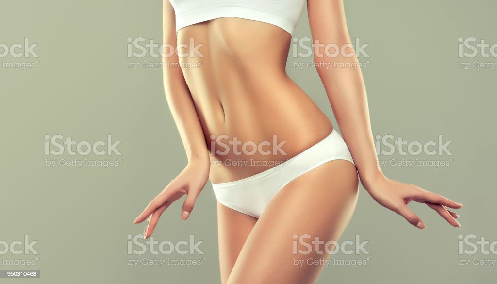 Graceful female is showing beautiful body, flat belly and elegant gesture. royalty-free stock photo