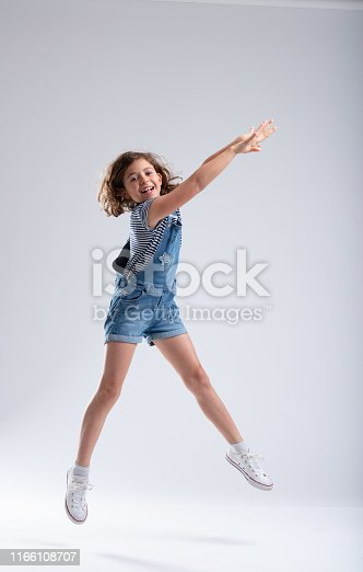 istock Graceful girl stretching her arms as she jumps 1166108707