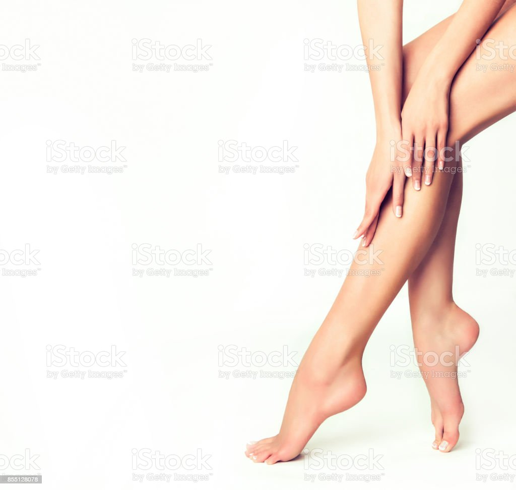 Graceful woman is touching well-groomed lags and feet. Close-up details of human body. stock photo