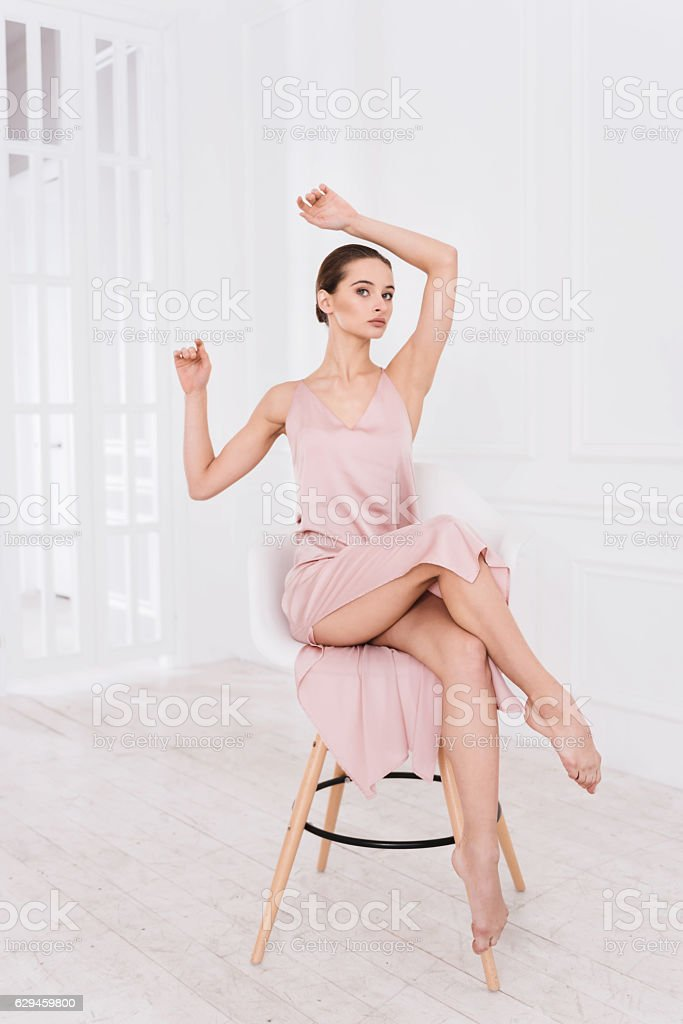 Graceful woman sitting with crossed legs stock photo