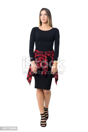 Front view of graceful young woman in black dress walking and looking away. Full body length isolated over white studio background.