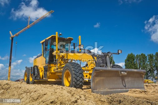 Working yellow Grader at a new highway construction against blue sky