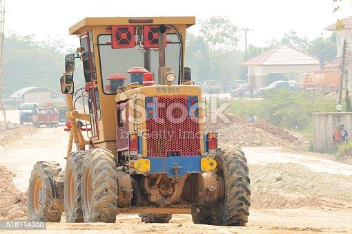 Grader leveling gravel on road construction site