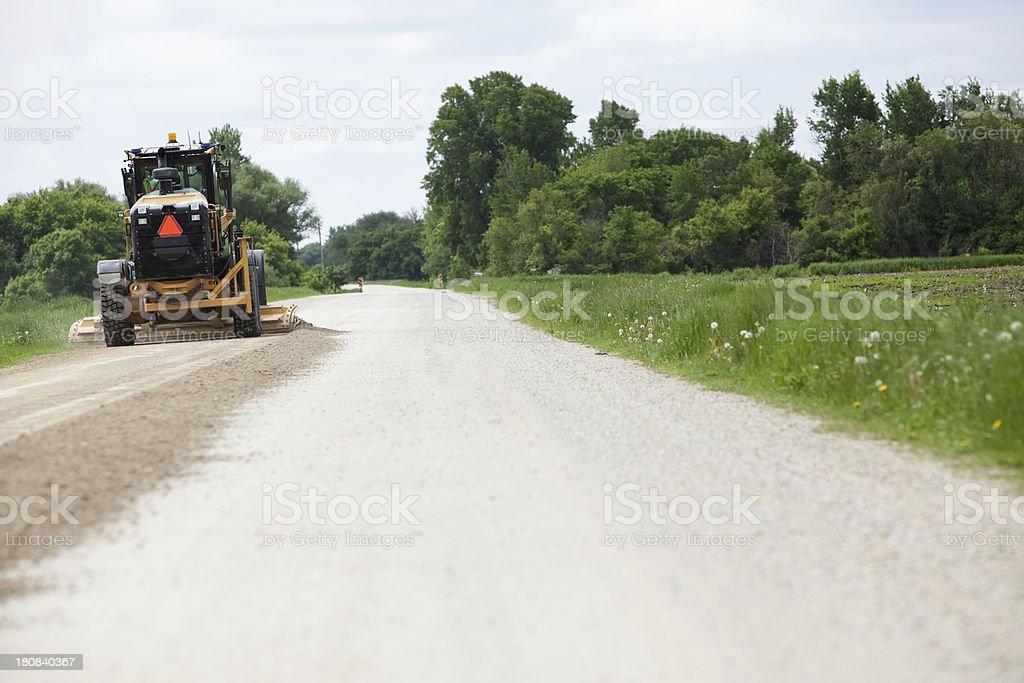 Grader Smoothing Gravel Road stock photo