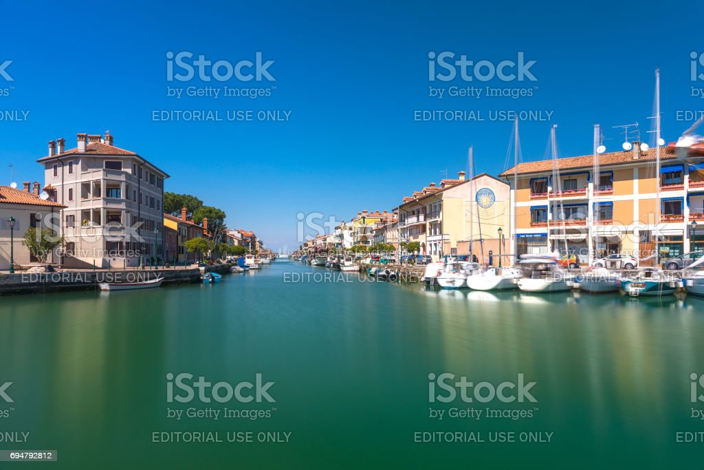 Grado, Italy: Canal with sail boats lying on water in small Italian town of Grado stock photo