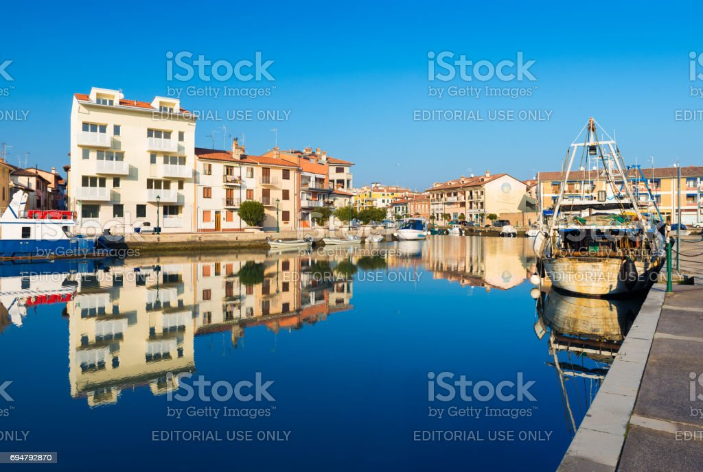 Grado, Italy: Colored houses and boats with their reflections in water of one of the canals of Grado stock photo