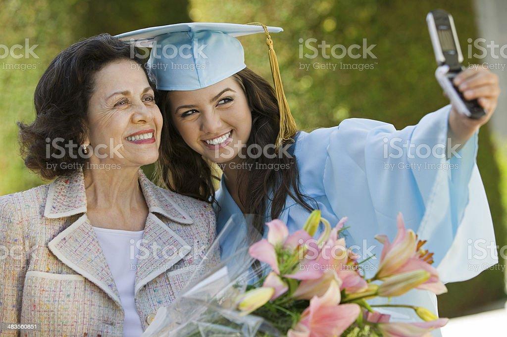 Graduate and abuela tomar foto con el teléfono celular - foto de stock