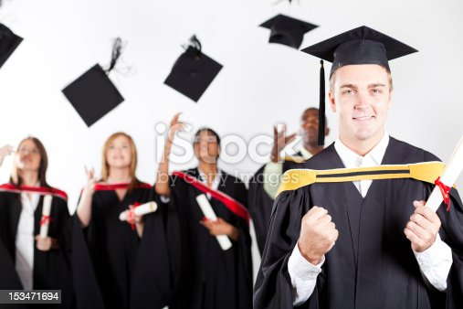 istock graduate at graduation with classmates in background throwing caps 153471694