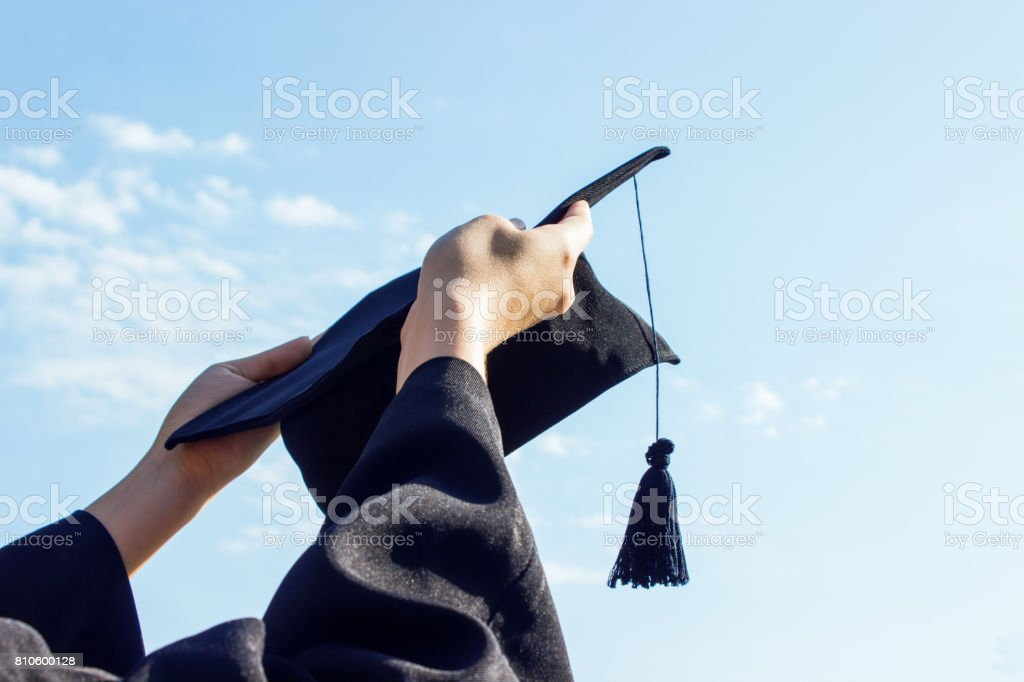 Graduate celebrating with cap in her hand,feeling so proud and happiness in Commencement day stock photo