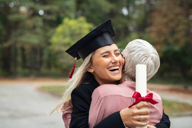 chica graduada abrazando a la madre - graduación fotografías e imágenes de stock