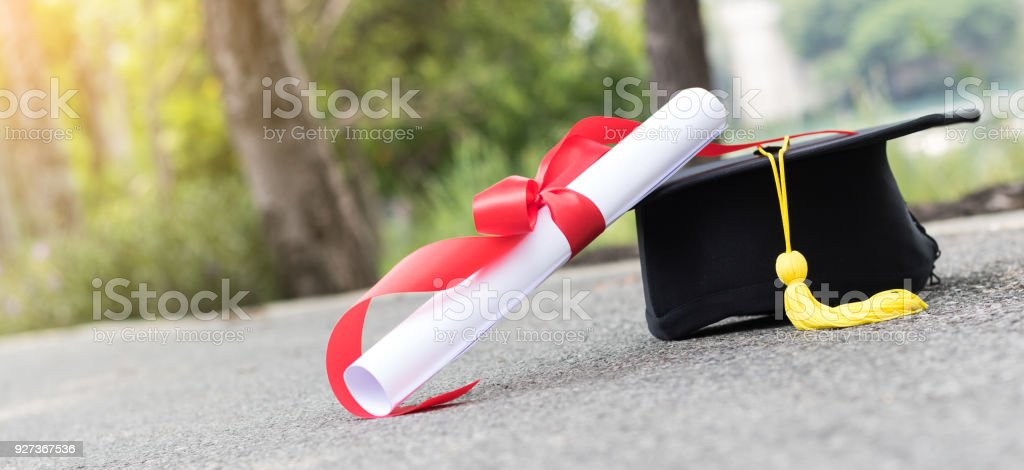 graduate hat and certificated on street graduate hat and certificated on street Achievement Stock Photo