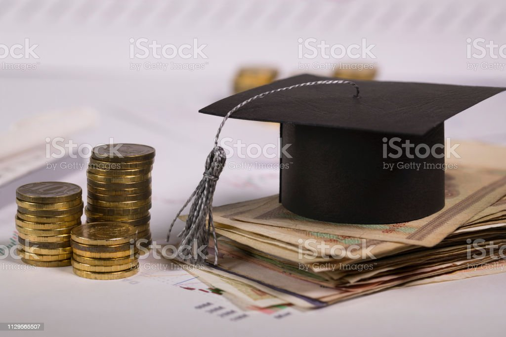Graduate hat on a pile of banknotes. Closeup